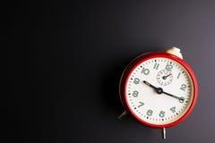 Rode wekker op zwarte achtergrond, Tijdconcept, Stormloop Stock Afbeeldingen