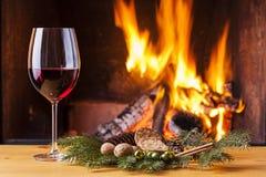 Rode wijn bij open haard die voor Kerstmis wordt verfraaid Stock Afbeeldingen
