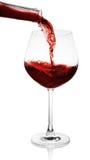 Rode wijn die in een glas wordt gegoten Stock Fotografie