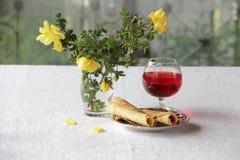 Rode wijn in een transparant glas, een boeket van rozen en wafeltje ro royalty-vrije stock foto's