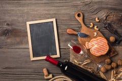 Rode wijn in een vakje met een glas, een kurketrekker en een roomkaas op een houten oude lijst stock afbeelding
