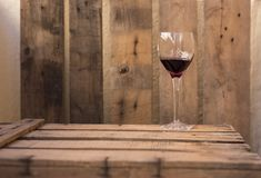 Rode wijn fijn cristal glas op een houten oude lijst Stock Fotografie
