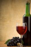 Rode wijn in glas en fles op hout stock afbeelding