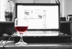 Rode wijn in glas met computerlaptop op houten lijst, die terwijl het werken ontspannen Stock Afbeelding