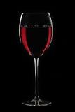 Rode wijn in glas op zwarte Stock Afbeelding