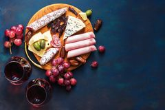 Rode wijn in glazen, voorgerecht, druiven, koud vlees, kaas met schimmel Delicatessensnacks op een blauwe achtergrond Hoogste men royalty-vrije stock foto's