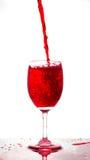 Rode wijn het gieten in een glas op witte achtergrond Stock Fotografie