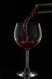 Rode wijn het gieten in een wijnglas Stock Foto's