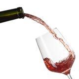 Rode wijn het gieten in glas met plons die op wit wordt geïsoleerd Royalty-vrije Stock Foto's