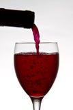 Rode wijn het gieten neer van een wijnfles Stock Foto's