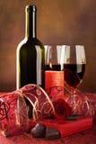 Rode wijn, kaars en chocoladeharten, stilleven stock afbeelding