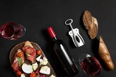 Rode wijn, kaas, kersentomaat, brood en prosciutto op houten raad over zwarte achtergrond, hoogste mening, exemplaarruimte Royalty-vrije Stock Afbeeldingen
