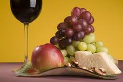 Rode wijn met druif, appel en kaas op een plaat. Stock Afbeeldingen