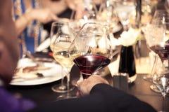 Rode wijn op hand met diner op restaurant Royalty-vrije Stock Foto