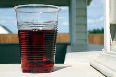Rode wijn in plastic glas stock foto's