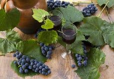Rode wijn in stemware die zich op de houten achtergrond met druiven en groene bladeren bevinden stock foto