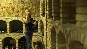 Rode wijn van glas drinken en vrouw die fles in kelder kijken Vrouw winemaker het proeven en het drinken rode wijn van stock videobeelden