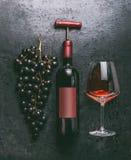 Rode wijnconcept met fles en uitstekende kurketrekker, glas en druiven op retro zwarte achtergrond, hoogste mening royalty-vrije stock foto's