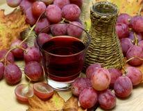 Rode wijnen eigengemaakte rieten fles en druiven Stock Afbeeldingen