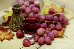 Rode wijnen eigengemaakte rieten fles en druiven Stock Foto