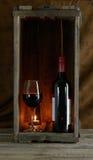 Rode wijnfles en glas in houten doos Royalty-vrije Stock Afbeelding
