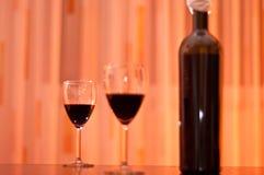Rode wijnfles en glazen Stock Foto's