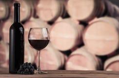 Rode wijnfles met glas op de achtergrond van eiken vaten De achtergrond van de wijn Stock Foto
