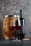 Rode wijnfles met glas voor het proeven en houten vat in donkere kelder royalty-vrije stock afbeelding