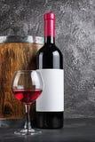 Rode wijnfles met glas voor het proeven en houten vat in donkere kelder royalty-vrije stock afbeeldingen