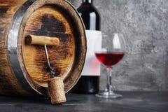 Rode wijnfles met glas voor het proeven en houten vat met kurketrekker in donkere kelder royalty-vrije stock afbeeldingen