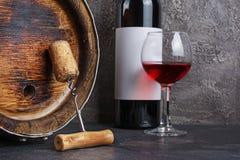 Rode wijnfles met glas voor het proeven en houten vat met kurketrekker in donkere kelder royalty-vrije stock fotografie