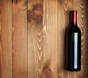 Rode wijnfles op houten lijstachtergrond royalty-vrije stock foto's