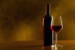 Rode wijnflessen en glas op houten lijst en zwarte achtergrond Stock Foto's