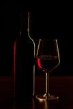 Rode wijnflessen en glassilhouet op houten lijst en zwarte achtergrond Stock Foto's