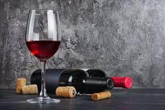 Rode wijnflessen met glas voor het proeven en kurketrekker in kelder stock foto's