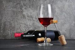 Rode wijnflessen met glas voor het proeven en kurketrekker in kelder stock fotografie