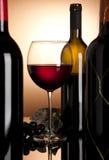 Rode wijnglas en flessen Stock Fotografie
