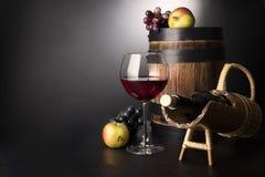 Rode wijnglas met fles in srawsteun en oud houten die vat door vruchten wordt omringd: wijnstok en appelen stock foto's