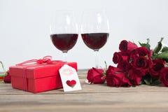 Rode wijnglazen, gift en rozen op houten oppervlakte Royalty-vrije Stock Afbeeldingen