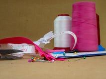 Rode, witte en roze kegels van naaiende draad met kleurrijke spelden royalty-vrije stock foto