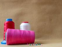 Rode, witte en roze kegels van naaiende draad met kleurrijke spelden royalty-vrije stock fotografie