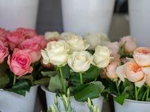 Rode, witte, roze boeketten van rozen die buitenkant storefront zitten van stock fotografie