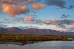 Rode wolken bij zonsopgang over de rivier stock fotografie