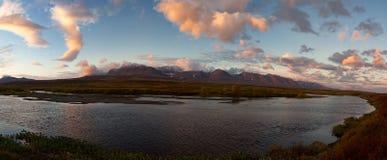 Rode wolken bij zonsopgang over de rivier stock foto's