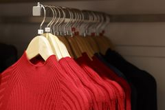 Rode wollen gebreide sweaters die op hangers in de opslag, close-up hangen stock foto's
