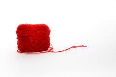 Rode wolstreng, breiend die draadbroodje, op witte backgrou wordt geïsoleerd stock fotografie