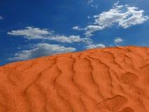 Rode zandheuvel in de woestijn rimpelingen in het zand met de wolken royalty-vrije stock foto