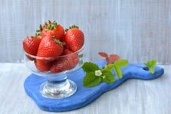 Rode, zoete, eigengemaakte aardbei in transparante schotel en tot bloei komende bloem op blauwe, houten raad Stock Afbeelding