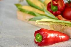 Rode zoete groene paprika in de voorgrond op grijze concrete oppervlakte dichte omhooggaand Vers groene paprika en graan op vage  Royalty-vrije Stock Foto's
