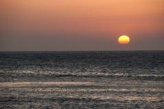 Rode zon en overzees bij zonsondergang Stock Foto's